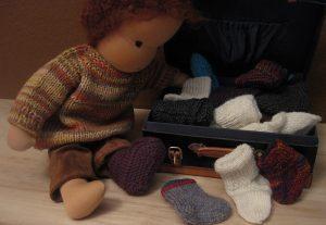 Puppe nach Waldorfart sucht im Koffer nach der zweiten Socke