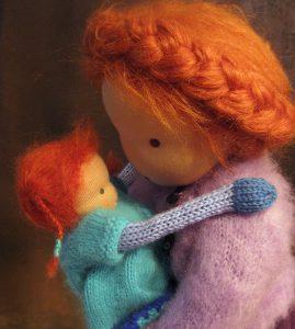 Große Puppe nach Waldorfart hält kleine Strickpuppe nach Waldorfart auf dem Arm