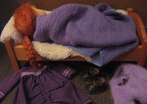 Rosalie-Puppe nach Waldorfart liegt in einem Puppenbett und schläft