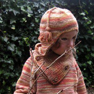 Kind im gestrickten Outfit in Herbstfarben