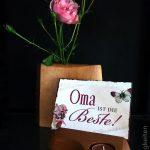 Vase mit Rosenblüte und Grußkarte im Kartenständer
