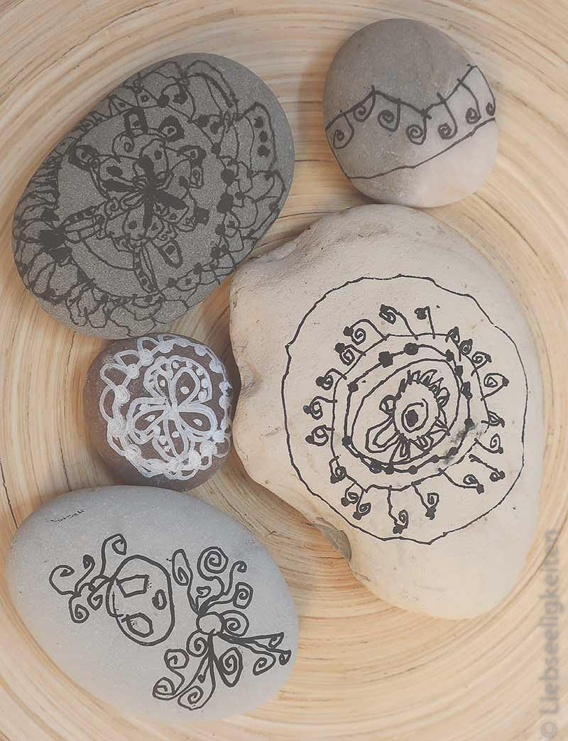 Gemalte Mandals auf Steinen einer Vierjärigen