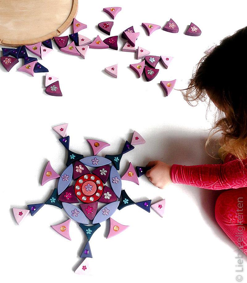 Kind beim Legen von Formen mit Steinen des Glitzermandals - Nachbau von Grimm