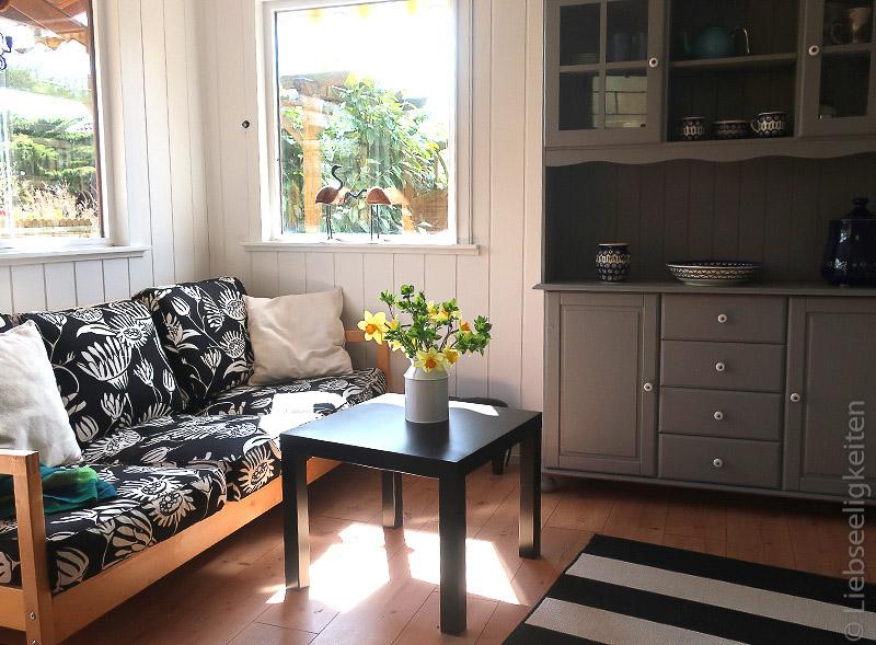 Gartenlaube - Sofa und grau gestrichener Küchenschrank in der Laube