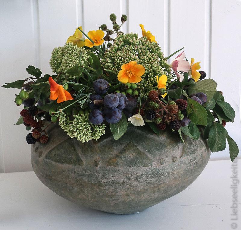 Blumenvase gefüllt mit herbstlichen Blumen und Früchten