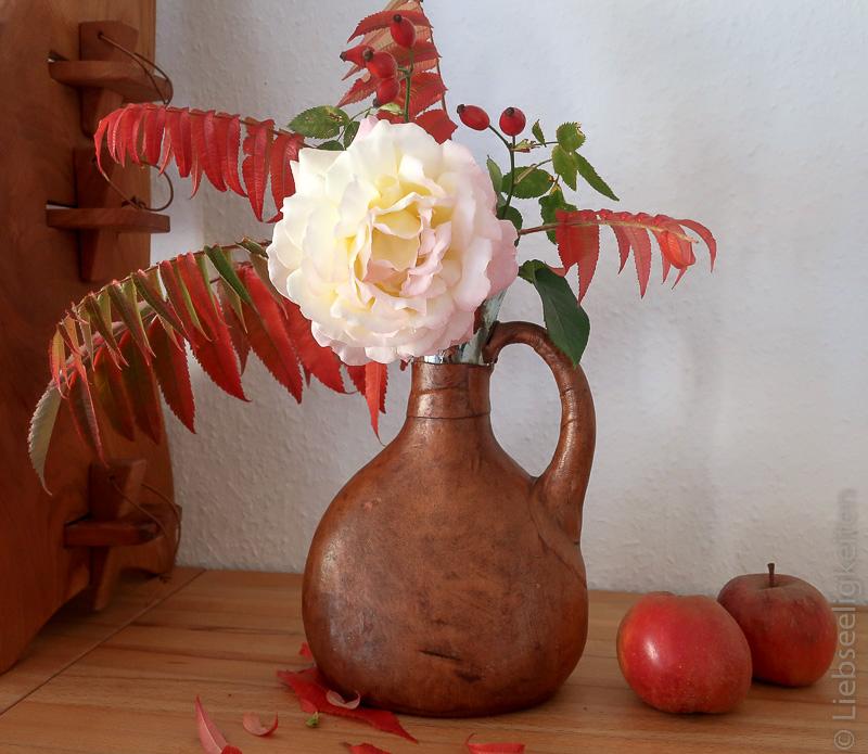 Rose Gloria Dei mit Herbstlaub des Essigbaums in der Vase