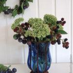 fette Henne , Brombeeren und Schlehen in der Vase